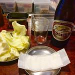 串かつ 七福神 - 瓶ビール(中)、450円。キリン、アサヒ、サントリーが選べる。そして、キャベツがセットされる。