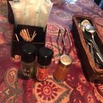 67866930 - テーブルにはカイエンペッパー、七味唐辛子、山椒が置いてあります。スプーンとフォークは不揃いです(^^)