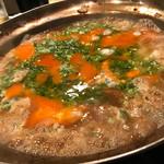 稲・もつ鍋焼肉 - モツ鍋のシメに雑炊を。女将が目の前で仕上げてくれますよ〜。