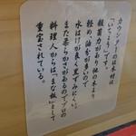 らーめん秋田 ひない軒 - カウンターに貼ってある云々。明るい色のカウンターです(^^)