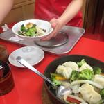 68431542 - 鍋蒸し餃子は野菜がたっぷりで嬉しい。特製の味噌ダレと食べるラー油風のタレをかけていただく。初めて注文したのだが、店員さんが丁寧に食べ方を教えてくれた。