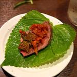 肉山 - モモ肉の上にチャンジャとキムチをのせて荏胡麻の葉で巻いて頂きます