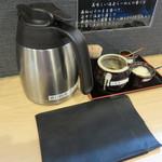 札幌らーめん 獅子王 - 卓上には、自家製ラー油・ニンニク・一味唐辛子・割りスープのポットが置かれています。 カウンター席後ろに、ティッシュや黒い紙エプロンも置いてあります。