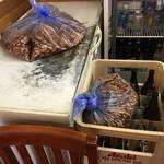 華隆餐館 - 内観(業務用冷蔵庫、ビールケースの上にビニール袋に入った四川落花生が雑に置かれている)
