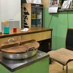 大衆酒場カネス - 煮込みの保温台とおかみさんの専用椅子