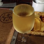 69279385 - こぼれプレミアム白ワインとお通しのポテトチップ
