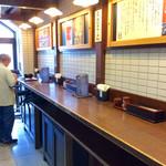 戎屋 - ⑦券売機の左横の暖簾をくぐると、イートインスペースがある。立ち食いで、標準で8人ほどが食べられそうな感じ。奥に先客が2名いた。