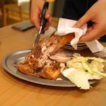 うどん酒場 香川一福 - 骨付き鶏 モモ焼き を切り分けております