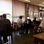 もつ煮屋 日の出食堂 - 『もつ煮屋 日の出食堂』椅子席、奥から撮影。満席、相席、それでも立ち待ち。