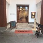 サルタヒコ - 建物の入口。1階が北九州文学サロンで、お店は2階に。