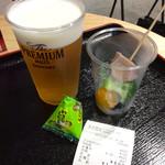 阪急梅田 ザ プレミアムモルツ ステーション - 「プレモル(400ml)」(400円)と「BBQ串」(100円)。ドリンクを頼んだ人は豆菓子も貰える。