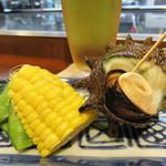 焼きやき亭 - お通しが出てきます。 夏らしく、枝豆・茹でトウモロコシ・サザエの壺煮。