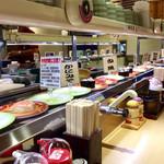 元禄寿司 - 店内風景。「特殊詐欺に注意」なるカードも廻っていた。1種類のネタにつき1〜2皿単位で流していて、多品種対応という廻し方だ。