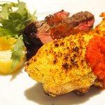 71223156 - メイン2種盛り 1500円 の本日の牛肉のグリル、鶏胸肉の香草パン粉石窯ロースト盛り合わせ