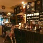 カフェ・ミエル - 振り子時計とカップが並ぶカウンター