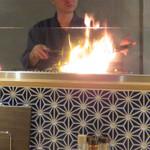 もも焼きト酒 おがた - カウンター席向こうの焼き場では、豪快にファイアーが上がってます。