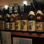 たくみ - カウンターの上にはお酒がずらっと並べられています。