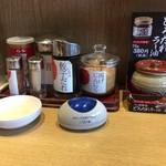 丸源ラーメン - カウンターの上。味変の材料が置いてます。