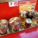 ラーメン山岡家 -   カウンターの調味料類