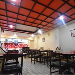 ぶたまん - 赤い格子の天井。 畳と椅子を組み合わせた不思議な作りのテーブル。