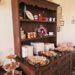 パティスリーアリス - エージング塗装を施したアンティーク家具調の棚に飾られた焼き菓子とマクミランアリスの食器たち