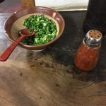 73573664 - 使い込まれたテーブルの上には青ネギと一味唐辛子
