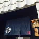 希須林 担々麺屋 - 入り口はこんな感じ。一面を白い瓦で覆った壁が印象的。