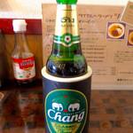 タイカレーラーメン シャム - 「チャーンビール」(小瓶、600円)。ボトルホルダー(非公式のグッズ)に入れられて出てくる。