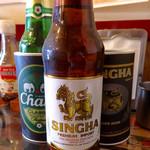 タイカレーラーメン シャム - 「シンハービール」(小瓶、600円)。こちらもボトルホルダーに入ってくる。なかなか楽しい。