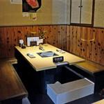 ギュウガテイ - テーブル席 下に白く見えるのは排気用のダクト
