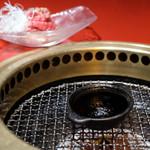 焼肉 綾小路 - 炙りユッケ 網の上のたれ皿を置いて熱くなったところで炙ります