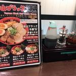 富山ブラック 麺家いろは - カウンター席の卓上。