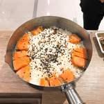 老記海鮮粥麺菜館 - 参考 澳門潜入工作レポート】日式三文魚煲仔飯。ガス火だと液体の対流は「外から内」である一方、卓上IHヒーターは「中から外」なので、具の並べ方を変え、このように仕上げる。