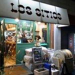 ロス・シティオス - お店の外観です。 白い大きな幌にLOS SITIOSって大きく店名が書いていますね。 壁は、グリーンとなっていますね。 窓が大きくとられており、開放的なお店となっていますね。 お店の中の楽しそうな様子