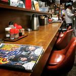 大明飯店 - 細長い店内の手前がカウンター、奥がテーブル席
