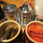 元祖名島亭 - 卓上には、ゴマ・コショウ・紅ショウガ・辛子高菜。 ニンニクはリクエストすれば持ってきてくれるそうです。