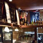 旬肴地酒 寅八 - 日本酒の一升瓶と蔵元の前掛けがオブジェとして飾られています