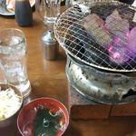 ホルモンまさる  - 炭火焼ですね!お冷と麦ご飯、わかめスープもきました 一番左がタレ付けるお皿…大きくカットされたお肉には小さい