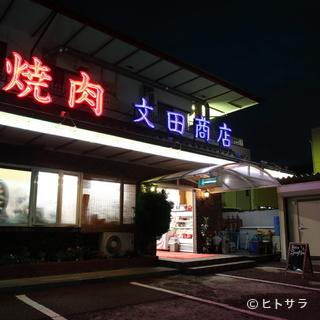 「焼肉文田商店」の大きな看板が目印