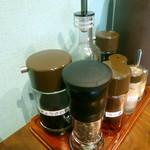 初代 山ちゃん - 「山ちゃん」卓上に置かれたミルに入ったブラックペッパー、コショウ、ラー油、酢、ニンニクペースト、餃子のタレ