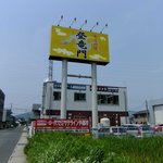 中国料理 登竜門 - 国道からは大きな看板と店舗の裏側が見えます