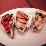 81949316 - 焼き牡蠣3種盛り。左からミニトマトとベーコンの焼き牡蠣、スモークチーズと黒胡椒の焼き牡蠣、アンチョビとガーリックの焼き牡蠣