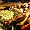 """ブロカント - 料理写真:当別浅野農場スマイルポーク、スペアリブの""""リブテックステーキ""""。 スペアリブを豪快に1枚焼きにしてみました。 濃厚で柔らかい、浅野農場自慢のお肉はステーキスタイルで。蒸したり煮たりすることのないステーキと同じ仕上げなので、その濃厚な旨味がギュッと濃縮されております。 カリカリに焼き上げた骨の周りのお肉もまた、手で豪快に掴みかじりつくのにぴったりです。お酒にとてもあう、そんな仕上がりですよ。"""