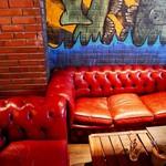 82547348 - でっかい真っ赤なソファは1部分が壊れていてお尻が床につきそうな感覚を味わえる