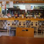 ひもの屋 Cafe&Bar - 店内の様子 カウンター席(焼酎や日本酒の瓶がたくさん置いてある)