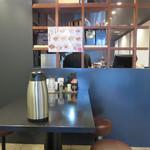 菜 - 入口付近に4人掛けテーブルが2卓、奥に厨房前のカウンターに8席あります。