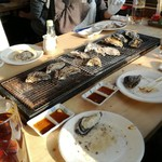 牡蛎処 桝政 - こんな感じでやいています。左側に蒸し器、ジョッキは烏龍茶