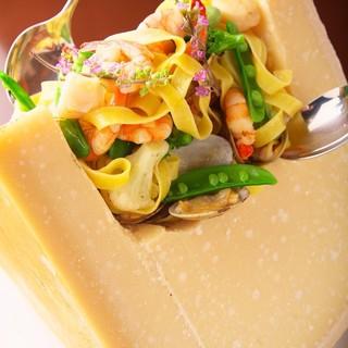 大きなチーズの中で仕上げる海老と旬野菜のタリアテッレ