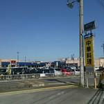オーパスワン - 道を挟んだ駐車場向こうは西友
