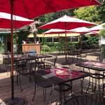 ラ・ブラスリー - 沢山のテーブルとパラソルがあるテラス